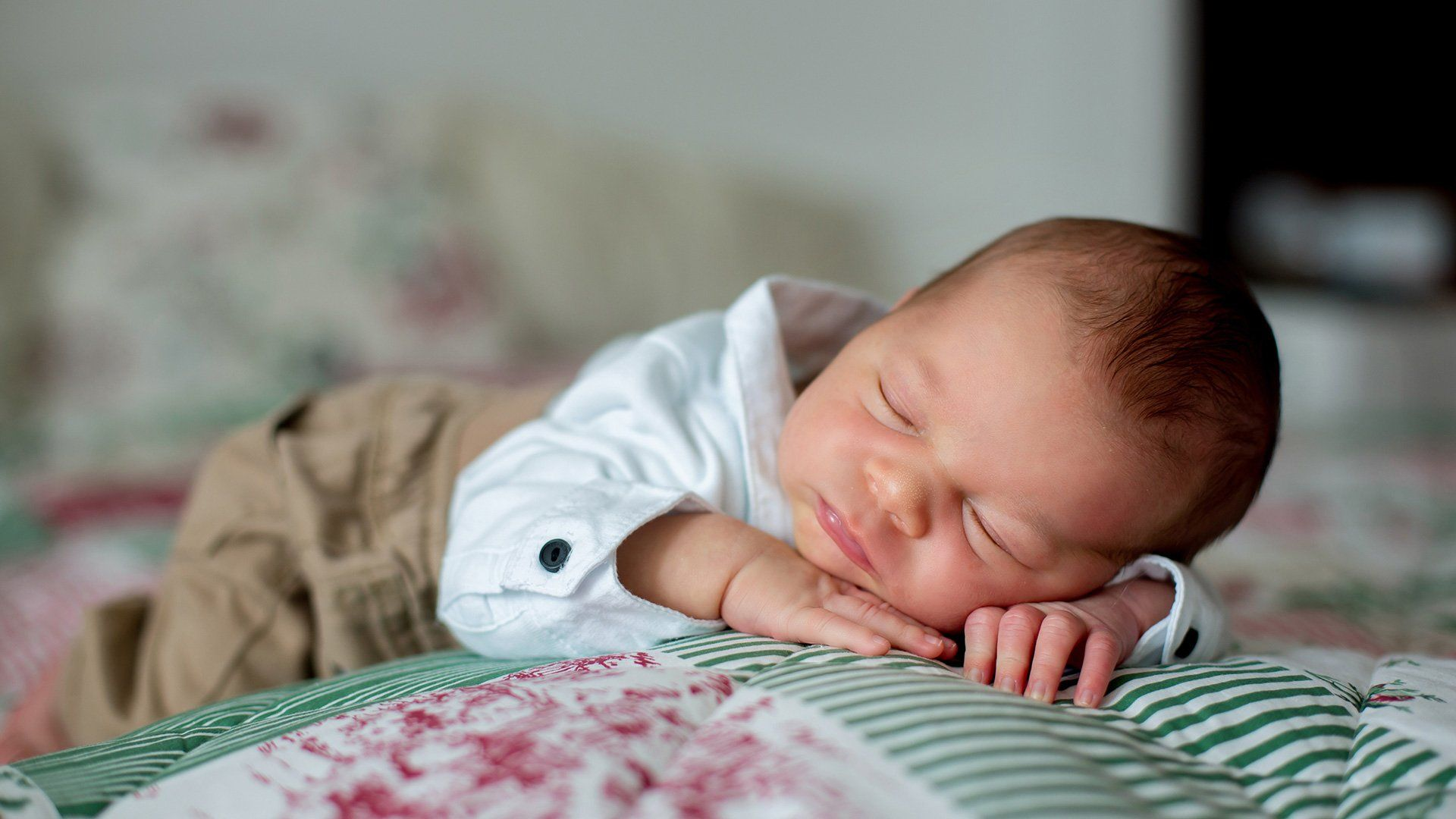 A baby wears a shirt and lies on its front on a green, pink and white blanket.